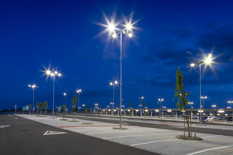big modern empty parking lot with bright LED street lights at night